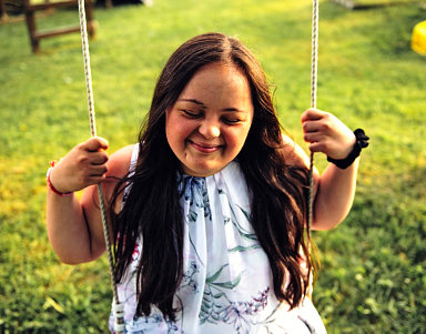 female child riding on a swing smiling