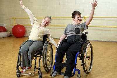 two children in wheelchair smiling