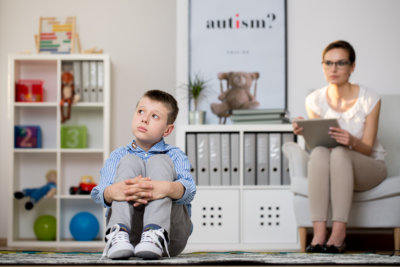 psychologist wearing glasses is looking at little kid sitting on carpet