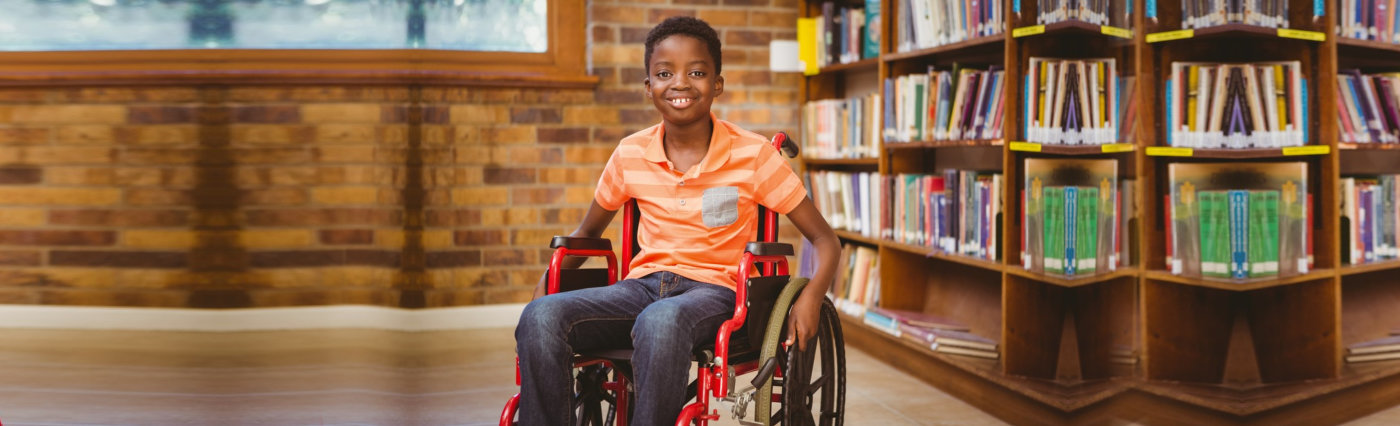 portrait of a little boy sitting in the wheelchair smiling